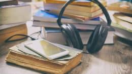 Lydbøger smartphone med høretelefoner ligger på en masse bøger